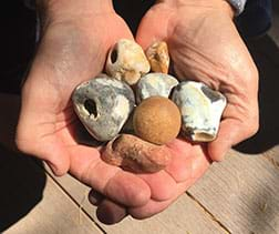 A photograph shows two cupped hands held together and holding about seven small, smooth and roughly round rocks of varying colors—white, gray, brown, orange.