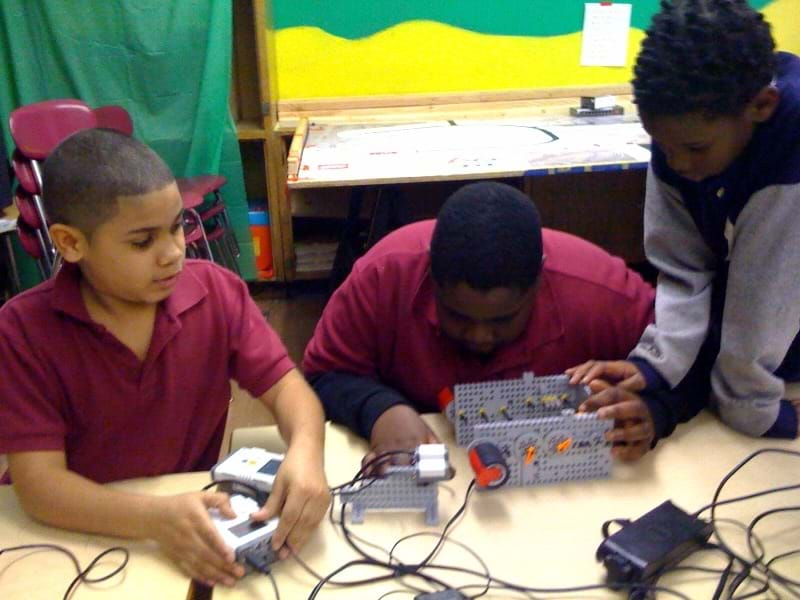 Three boys at a table set up their experiment by preparing the robot, fixing the gears and setting up the light sensor.