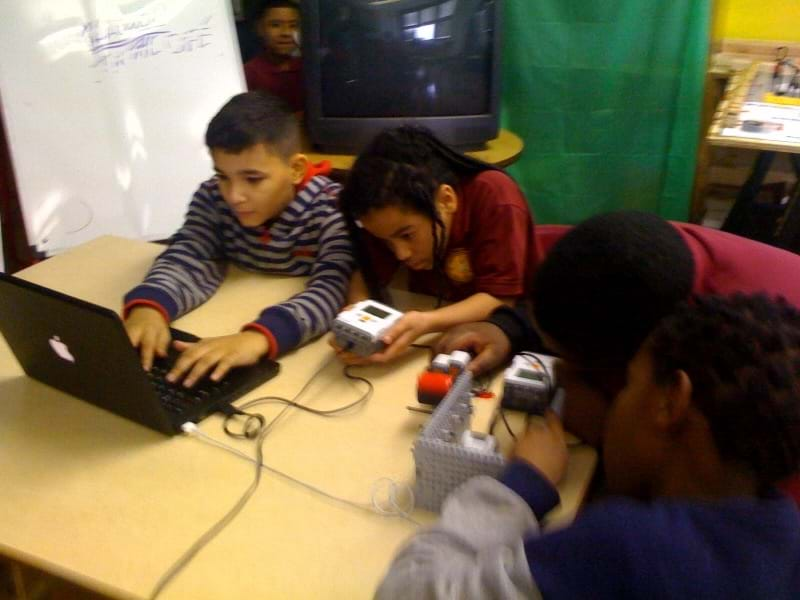 A photograph shows four students at a table working with a laptop, LEGO brick and the experimental setup made from LEGO components.