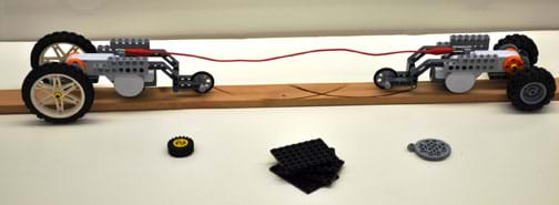Photo shows two three-wheeled robots facing each other at opposite ends of a board, with a string between them, attached to each. In front are extra pieces, a wheel, a gear and some LEGO pieces.