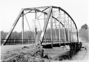 A black and white photo shows a deck bridge, with large trusses on the top of the bridge.