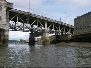 Photo shows a deck bridge, with large trusses below the bridge.