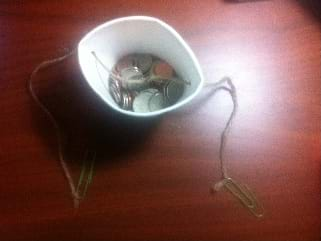Photo shows a paper cup partially filled with coins. A string runs through two holes on opposite sides of the cup near the rim of the cup. Each end of the string is tied to a paper clip.