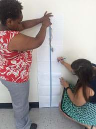 A photograph shows two female teachers testing the activity. One drops Washy tied to a few rubber bands while the other observes, measures and records the resulting displacement from the fall on paper taped to the wall.