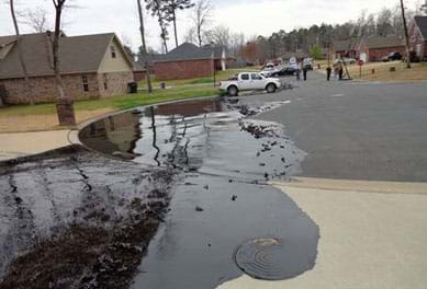 A photograph shows the black slick of an oil spill on a residential cul-de-sac street, spilling over a concrete driveway and contained in a pool by a curved concrete curb. The crude oil spill came from a rupture in ExxonMobil's Pegasus 850-mile IL-to-TX pipeline in Mayflower, AR, in 2013.