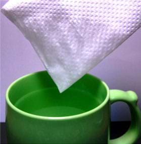 A photograph shows a folded paper towel with one corner just pulled out of a mug of water. Water from one tip of the paper towel has absorbed upwards to moisten a big area.