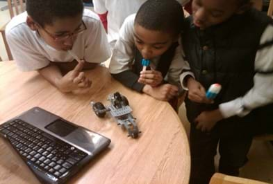 A photo graph of three young boys experimenting with a LEGO vehicle.