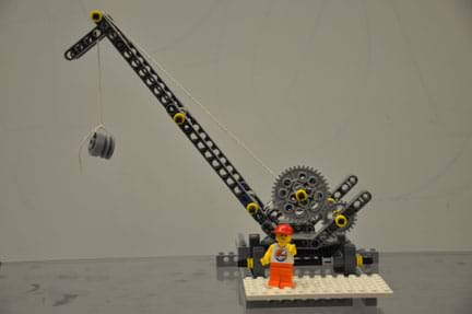 Photo shows a construction crane built of LEGO pieces with a LEGO construction worker.