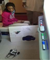 A photograph shows a girl observing a robot moving to avoid its surrounding low walls.