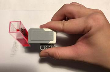 A photograph shows a hand holding a plastic LEGO device with one end touching a plastic container (shaped like a squared-off test tube) of red liquid.