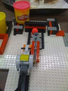 A photograph shows a LEGO compressor device working to compress a Play-Doh sample.