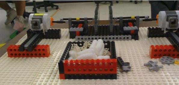 A photograph shows a LEGO raised-dots platform composed of various LEGO bricks, compressors and motors.
