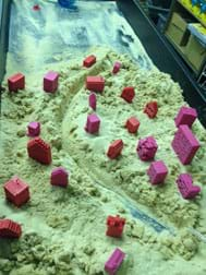 A photograph shows a curving canyon (river pathway) cut through a mass of sand on which a scattering of 20+ miniature pink and red buildings are placed.