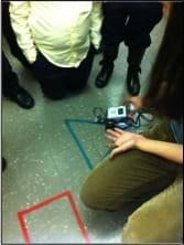 Several students and a teacher gather around a LEGO robot that is traveling the perimeter of a taped triangle on a linoleum floor using the robot's light sensor and programming that directs the robot to follow a colored line.
