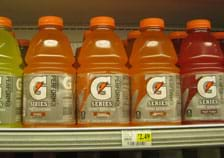 Photo shows five 32-ounce (846 ml) jugs of yellow, orange and red Gatorade sports drink on a grocery shelf.