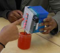 Photo of a hand holding a box with lighted LED bulbs, its probes inserted into a beaker of red liquid.