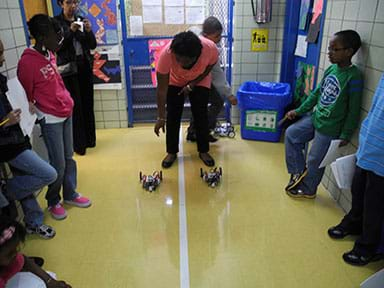 Photo shows teacher releasing two robotic racers as students line a linear racetrack in a school hallway.