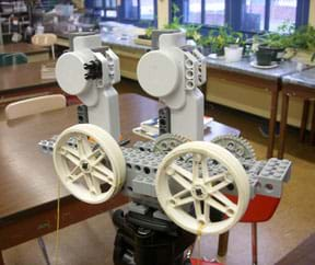 A photograph shows the LEGO MINDSTORMS NXT pulley and gear system used in this activity, mounted on a tripod in a classroom.