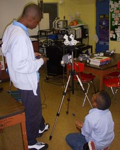 A photograph shows two boys in a classroom near a tripod with a device four-wheeled LEGO device mounted on it. Source/Rights: 2012 Jeffrey Laut, AMPS, NYU-Poly