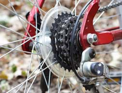 A photograph of the hub of the center of a back bicycle wheel shows the rear gears—a stack of six toothed wheels (sprockets), each with a different number of teeth.