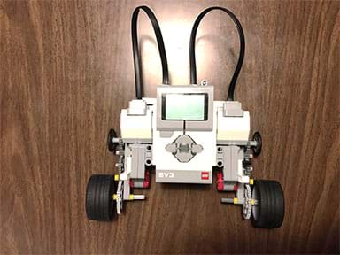 A photograph shows a LEGO EV3 robot composed of a brick-sized computer (a palm-size plastic device with buttons and display) with two servo motors, each attached to a three-gear drive train and two beefy 4x4 wheels.