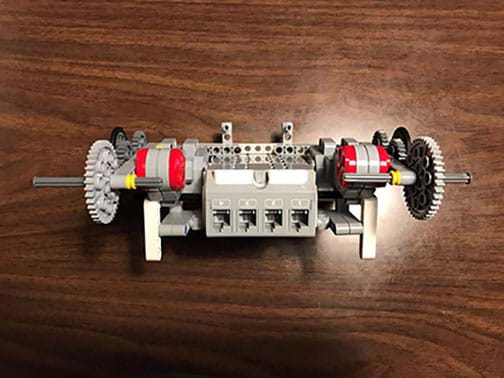A photograph shows a LEGO EV3 robot—a shoebox-sized device made of plastic components. The view shows the four-port side of a LEGO EV3 brick with two attached servo motors, each attached to multi-gear drive trains with axles (no wheels are attached in this view).
