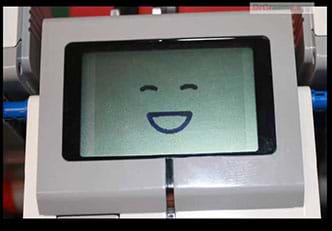 A photo of handheld plastic device with a small display screen and buttons. The display image is a smiley face.