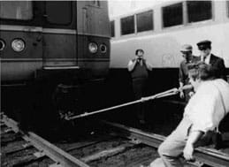 A black and white photo shows a man leaning back on the tracks as he bites on a rope connected to a train car.