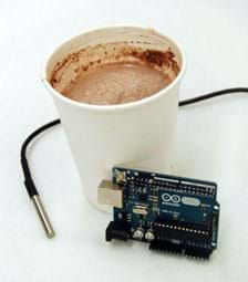 A photograph shows a cup of hot chocolate with an Arduino (microcontroller circuit board) and DS18B20 thermal sensor (long black wire with silver metal probe end) nearby.