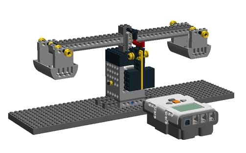 The image shows the final construction of LEGO balance scale created with a computer graphics program. The overall design is a two-sided balance, with a LEGO brick in front.
