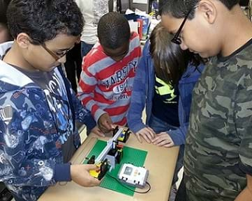 A photograph of four students interacting with the LEGO Balance Scale