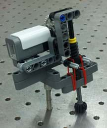 Photo shows a pressure sensor comprised of a rotation sensor, rubber bands, and other LEGO pieces.