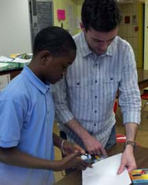 Photo shows a sixth-grade student and a GK-12 fellow (a college engineering student) at a table with a hand-held device and a piece of paper.
