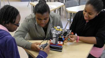 Photo shows three teens around a table working on a LEGO robot.