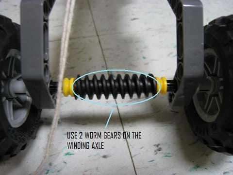 Photo shows a screw-shaped bar between two wheels with the note: Mount two worm hears on the winding/driving axle.