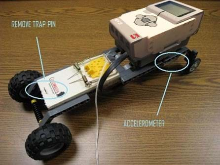Photo of a mouse trap race car shows the brick and accelerometer over the back wheels, and the mousetrap pin removed.