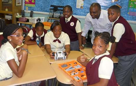 A photograph shows six students and a teacher working with a LEGO robot.