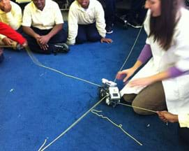 Three students and a teacher observe the collision of two LEGO robots where two lines of yarn cross on a carpeted floor.