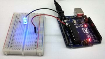 A photograph shows an Arduino Uno microcontroller connected to a clear LED (lighted bulb) via two jumper wires, a breadboard and a resistor.