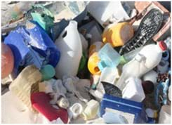 A photograph shows a pile of many different types of plastics found in a garbage dump: beverage, liquid and food containers and their caps and lids, shoe soles, buckets.