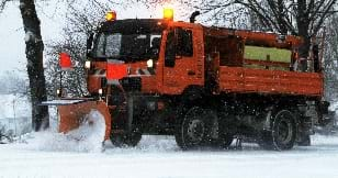 An image of a large orange truck with a snowplow attached to the front, pushing snow along a tree-lined road.