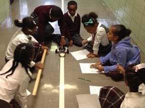 A photograph showing seven students in a semi-circle around the robot testing station. A robot pushes a container of sand along the length of track.