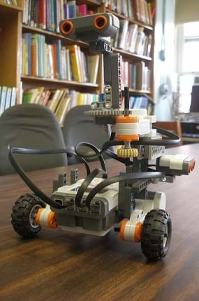Photo shows a small wheeled robot on a table top.