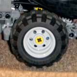 Photo shows a toy wheel made from a flexible black treaded plastic tire and a hard grey plastic rim.