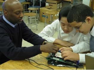 Photo shows two students constructing a traffic light circuit on a breadboard. An adult is assisting with the construction of the board.