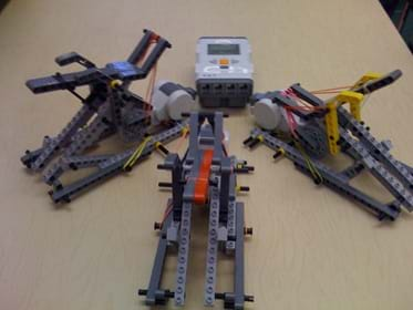 Photo shows three tabletop-sized devices made from LEGO pieces and rubber bands, with a LEGO brick sitting nearby.