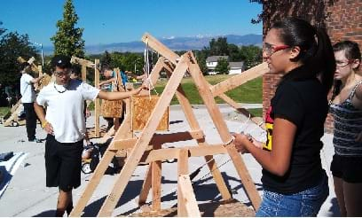 A photograph shows students preparing to launch a trebuchet designed and built during a summer high school course.