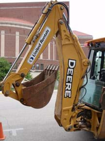 Photo shows a backhoe boom, dipper stick and bucket.