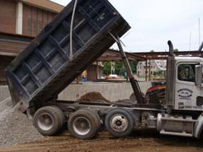 Photo shows a dump truck unloading a load of gravel.