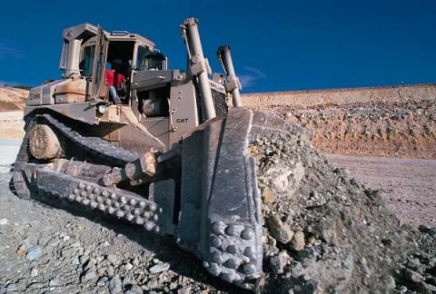 Photo shows a heavy industrial bulldozer pushing a massive amount of rocky soil.